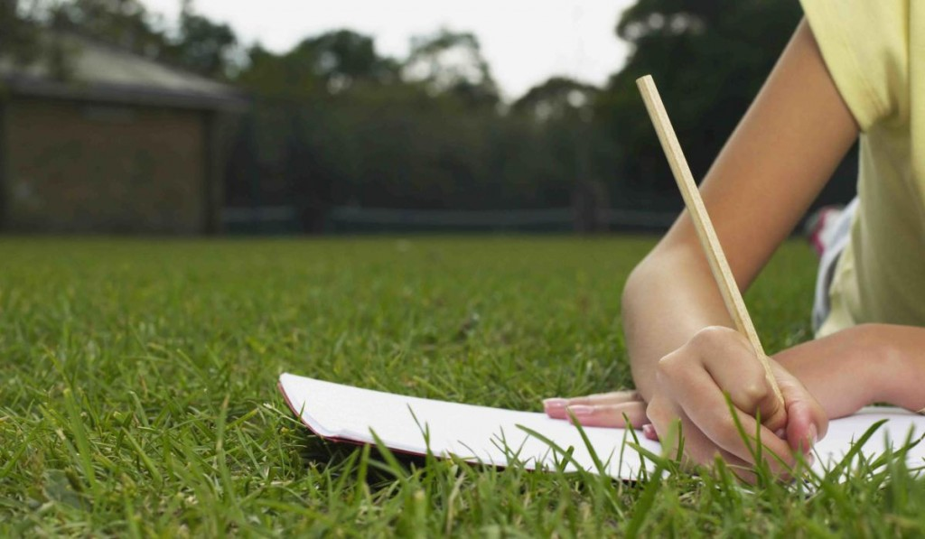 Girl doing homework in a park --- Image by © Image Source/Corbis